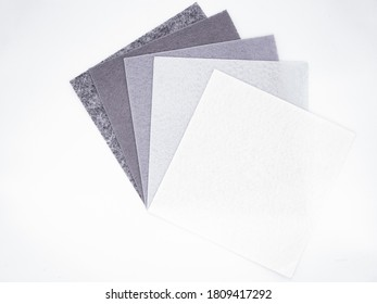 Five square pieces of felt of different shades of gray from dark to very light, isolated. Grey spectrum. Copy space