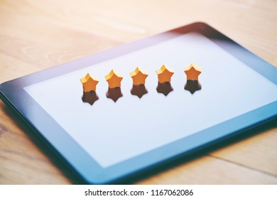 five stars rating symbol as product feedback on tablet computer