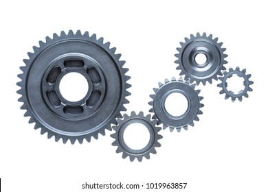 Five steel cog wheels from an engine are connected together over a plain white background.