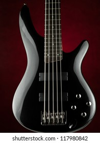 Five string electric bass guitar over red background, for music,entertainment themes