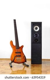Five string electric bass guitar on a stand next to a floor-standing loudspeaker