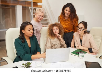 Five successful ethnically diverse women of different age watching something on laptop in office horizontal shot