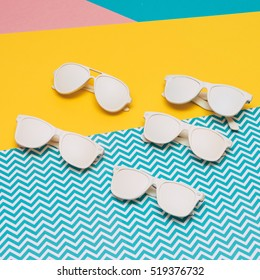 five sunglasses of different shapes laid out on the colored background. white painted goods.