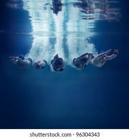 Five swimmers jumping together into water isolated blue background