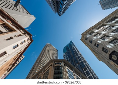 Five tall buildings viewed from bottom looking up with blue sky during the day