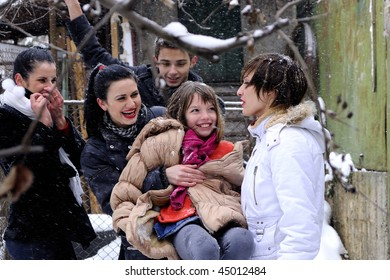 five teenagers playing in snow