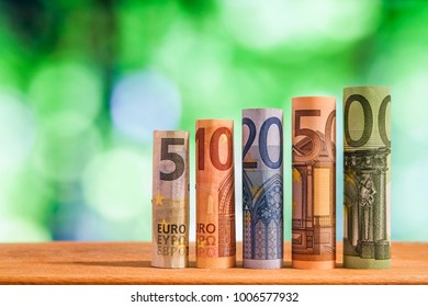 Five, ten, twenty, fifty and one hundred euro rolled bills banknotes on green blurred bokeh background