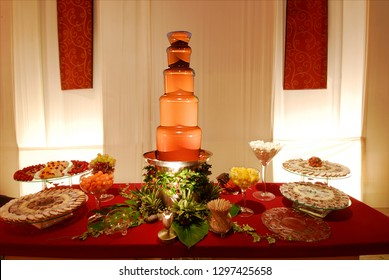 Five tiered chocolate fondue fountain and lavishly decorated dessert table with flowers, fruits and delicacies.
