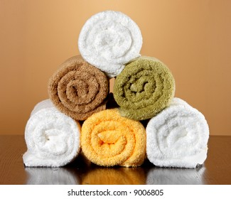 Five towels stacked up on a table with a reflection