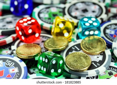 Five translucent colored dice laying on a pile of gambling chips of various denominations., with some gold coins also lying on the gambling chips