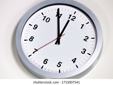It is five to twelve, the clock is ticking. Modern white grey clock shows the time 5 before 12. Close up to a wall clock, with five minutes to twelve o'clock. Time is running out