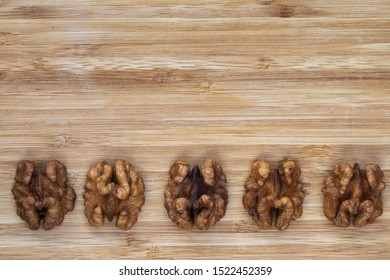 Five unshelled walnuts lie in a line on a brown wooden background from below, above is an empty place, top view, close-up