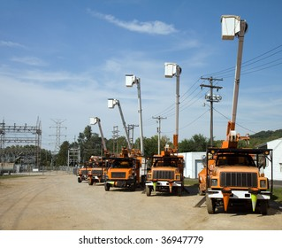 Five utility bucket trucks parked beside an electrical substation.