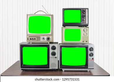 Five vintage televisions on old wood table with chroma key green screens.