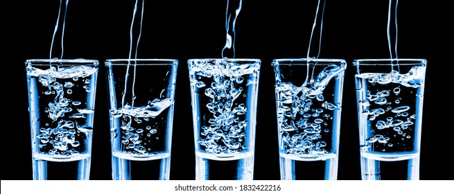Five vodka shots in a row isolated on black. Transparent neon alcohol glass background. Pouring cold vodka from hight. Booze splashing into glass. Fizzy bubble liquid liquor.