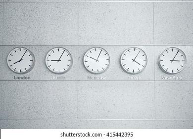 Vijf wandklokken tonen tijd in verschillende hoofdsteden van de wereld.