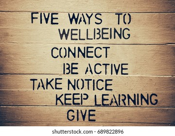 Five Ways to Wellbeing in black letters on textured wood panel background