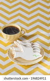 Five white (dove shaped) Cookies on yellow plate with steaming coffee