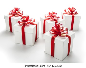 five white festive gift boxes with red bows on a white