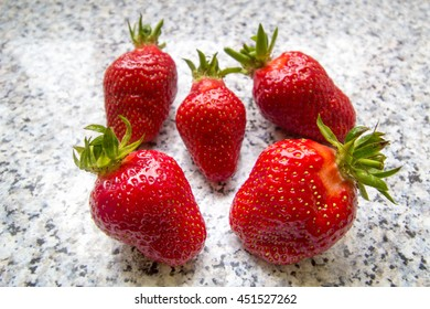 Five whole fresh strawberries from above on a kitchen counter
