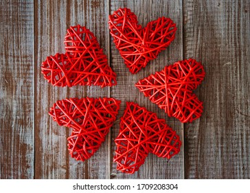 Five wicker red hearts lie on a wooden table in the shape of a flower, top view. The weave of the paper. Valentine's day, symbol of tender, fragile feelings, Wedding day. Family of five members.