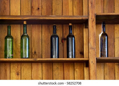 Five wine bottles without label in an old wooden shelf