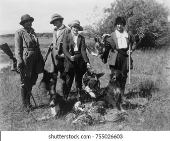 Five women hunters posed with their guns, dogs, and dead birds, ca. 1920.