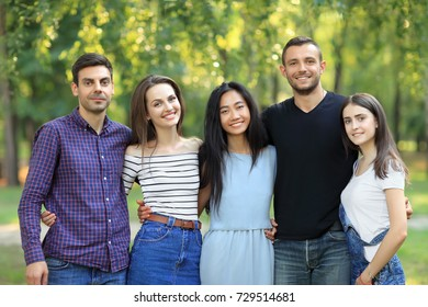 Five women and men friends on green forest background. Half body portrait of multi racial friends in park on summer sunny day. Beautiful happy carefree people, friendship concept