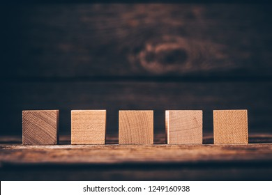 Five Wooden Cubes on Wood Background with Copyspace
