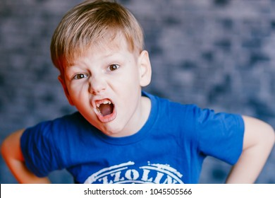 five year old boy grimaces and open his mouth in front of the camera