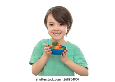 Five year old boy holding bowl of healthy food, isolated on white background. Smiling six year old child with vegetables, broccoli and carrots. Elementary school wellness and healthy eating concept.