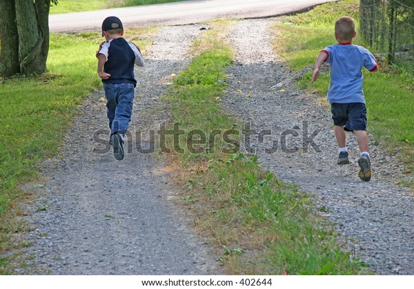 Five year old boys racing to the end of drive.