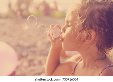 Five year old caucasian beautiful little girl blows soap bubbles on a summer beach on a sunny hot day. Happy carefree childhood. Toned orange purple effect.