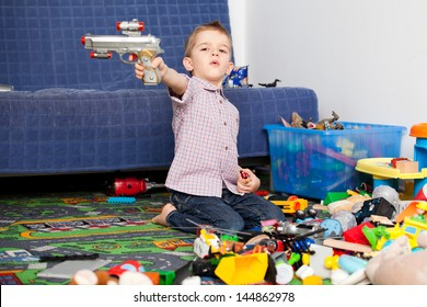A five year old child playing in his room with a lot of toys around him. A five year old boy pointing at something/someone with his toy gun