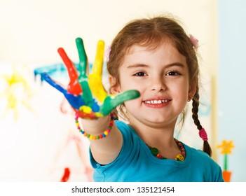 Пятилетняя девочка с руками окрашены в красочные краски, готовые для отпечатков рук