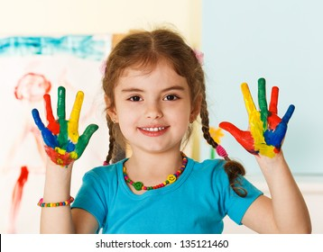 Five year old girl with hands painted in colorful paints ready for hand prints