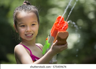 Five year old girl playing with squirt toy outside on a sunny day.