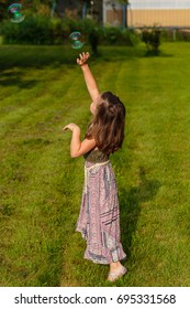 Five year old girl reaching for a soap bubble