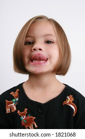 five year old girl trying to touch her nose with her tongue