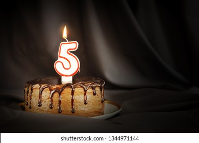 Five years anniversary. Birthday chocolate cake with white burning candle in the form of number Five. Dark background with black cloth