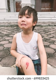 Five years old boy crying because run down and Bloody abrasions on the knee (selective focus) / Children often enjoy playing until they forget to watch out for their own safety