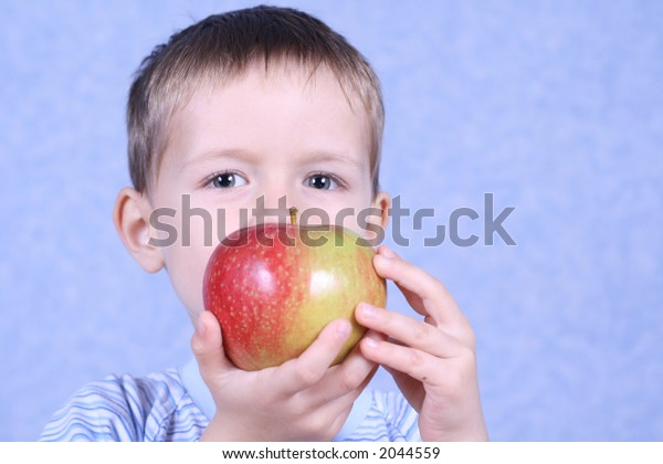 five years old boy eating red apple