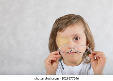 Five years old boy with one eye covered by eye pad and with eye glasses.