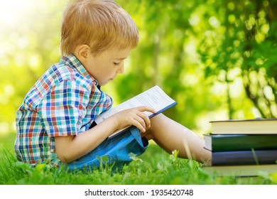 Five years old child sitting on the grass and reading a book
