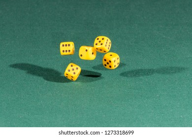 Five yellow dices falling on a isolated green table