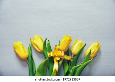 Five yellow fresh tulips on a silver grey background with a yellow ribbon and copy space. Concept of holiday, March 8, International womans day. Card with copy space. Colors of the 2021 year