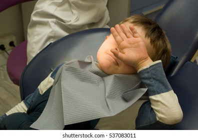 Five y.o. boy doesn't want to make a stock photo sitting in the dentist chair under the medical lamp light and closing face by his arm