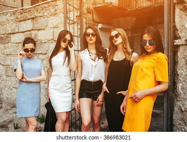 Five young beautiful girls posing against the backdrop of an abandoned building