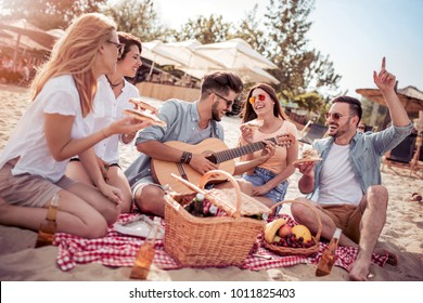 Five young cheerful people eating pizza and drinking cold beer while sitting on the beach.
