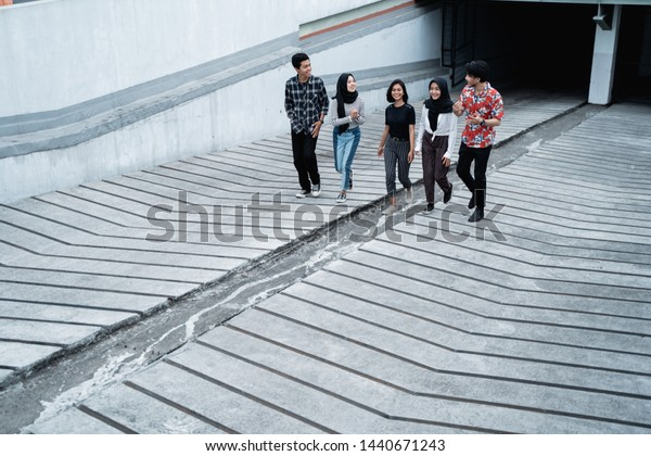 Five young friends walking posing on the way together when hanging out